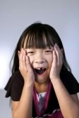 8425690-cute-little-chinese-girl-raises-her-hands-to-her-face-in-surprise